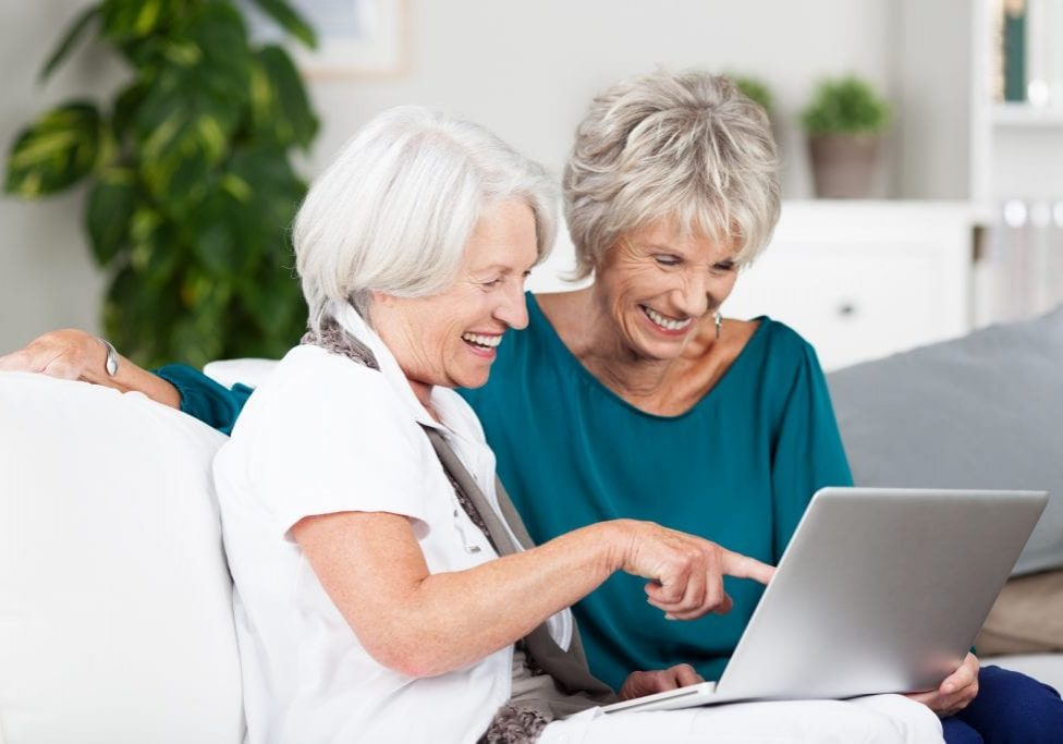 Two senior women surfing the internet laughing and exclaiming as they point to something on the screen while sitting side by side on a sofa in the house